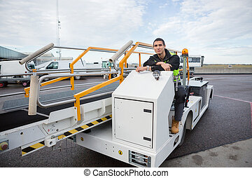 Confident Worker Sitting On Luggage Conveyor Truck -...