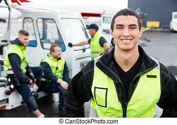 Confident Worker Smiling While Colleagues Communicating At...