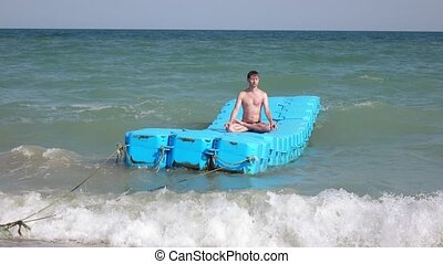 Yoga at the sea nature - Floating on a man practices yoga...