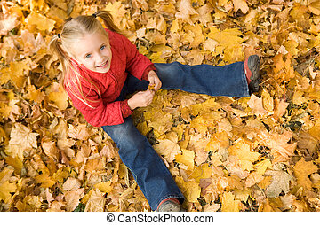 Autumn mood - Above view of smiling girl sitting on autumnal...