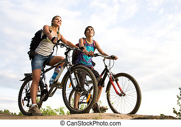 Two cyclists - Image of sporty couple on bicycles outdoors...