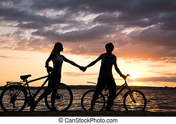 Evening stride - Silhouettes of couple holding each other by...