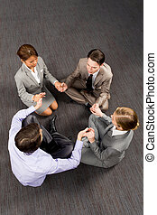 Praying together - Above view of business people sitting on...