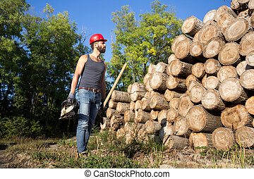 Lumberjack with chainsaw and ax in forest - Young attractive...