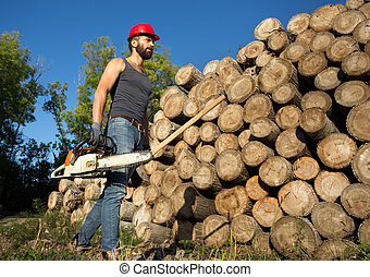 Lumberjack with chainsaw and ax beside trunks - Young...