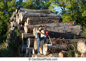 Lumberjack with chainsaw and ax on trunks - Young attractive...