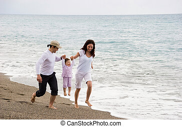 Strolling - Photo of modern family running down seashore and...
