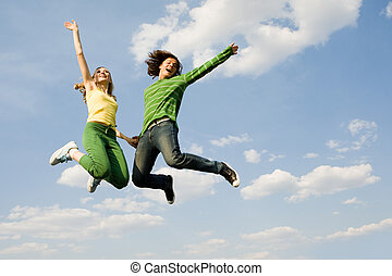 On cloud nine - Image of cheerful girl and guy jumping high...