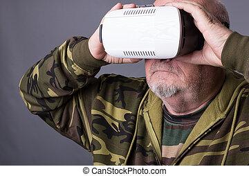 Senior man in wearable technology VR glasses. Confident old...