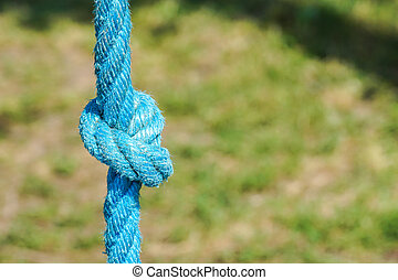 Tied knot on a blue rope isolated on green park .
