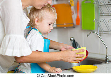 Mother teaches little son dish cleaning in domestic kitchen