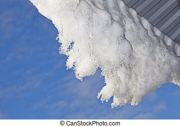 Snow hanging from the roof in front of blue sky