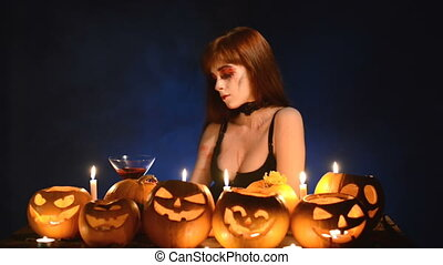 Woman with Halloween pumpkins holding cocktail glass - Sexy...