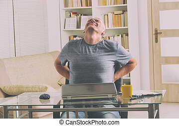 Man suffering from low back pain - Man in home office...