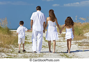 Mother, Father and Children Family Walking At Beach - Rear...