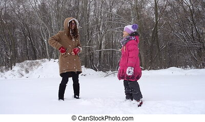 laughing sisters having fun at the snowy winter day