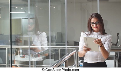 Portrait of sexy business woman in glasses with a tablet