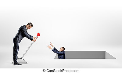 A businessman turns a large lever helping another man fallen inside a large square hole in the ground.
