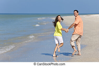Happy Couple Running Holding Hands on A Beach - Happy man...