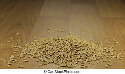 Hand quickly pours the barley grains from a wooden spoon...