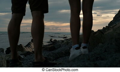 Man and woman hold hands and in evening watching sunset in...