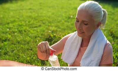 Delighted aged woman drinking water after sport activities -...