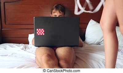 Sexy woman trying to seduce man working on laptop in bed....