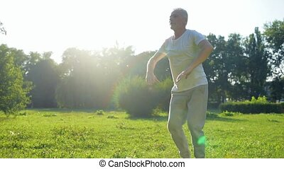 Tracking of a sporty aged man squatting in the park - Take...