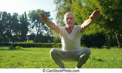 Cheerful elderly man squatting outdoors - Best way to rise...
