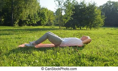 Senior sporty man doing adbominal crunches in the park -...
