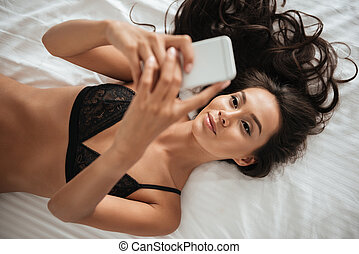Young beautiful asian woman in lingerie taking a selfie -...