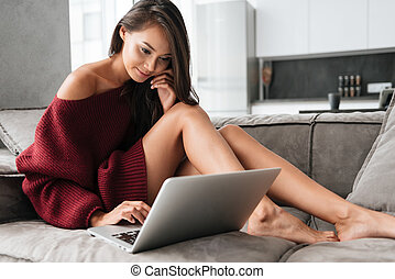 Smiling pretty asian woman in sweater using laptop while...