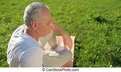 Positive elderly man resting after sport exercises
