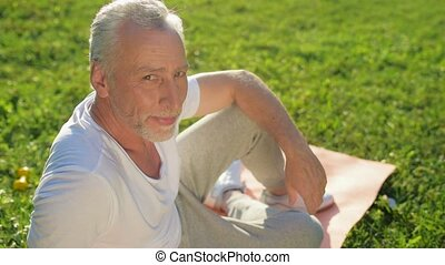 Positive aged man resting after sport exercises outdoors