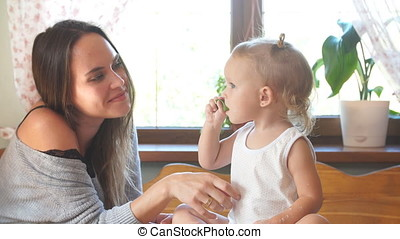Young mother and daughter spending time in the kitchen