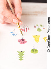 Side view of artist drawing flowers design at workplace -...