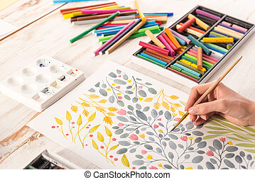 Top view of artist drawing flowers design at workplace - Top...