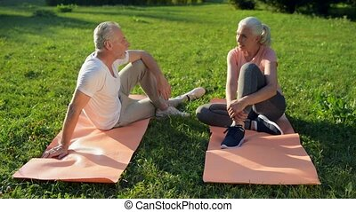 Joyful sporty aged couple resting after sport activities -...