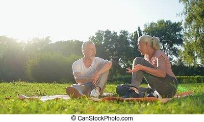 Joyful elderly couple starting doing physical exercises in...