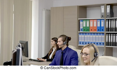 Sales marketing team in the office talking on the headphone...