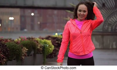 Cheerful mixed race woman starts running along city park...