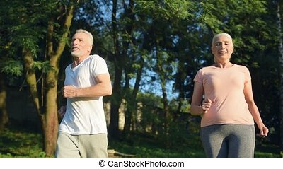 Positive sporty sneior couple enjoyign jogging outdoors