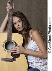 A girl and her guitar - young brunette girl leaning on...