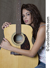 hugging the guitar - young brunette girl hugging an...