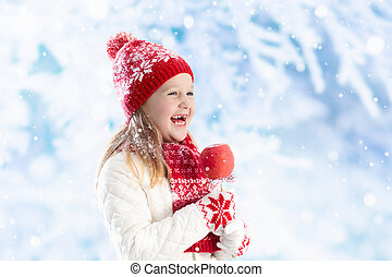 Child with candy apple on winter fair - Child eating candy...