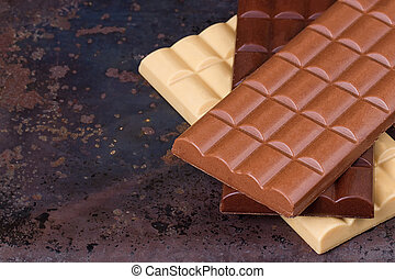 milk, dark and white chocolate bars on grunge background