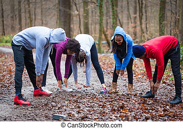 Young group of people warming up the upper-body outdoors