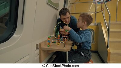 Dad and son spending time in train play room - Boy and his...