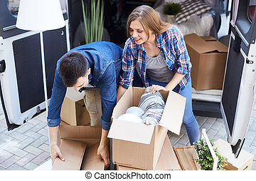 Couple Unpacking Boxes for Moving In - Young couple, man and...