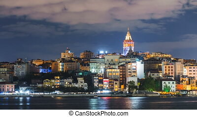 Istanbul cityscape with Galata Tower and floating tourist boats in Bosphorus night zoom in timelapse